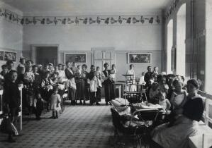 view University Children's Hospital, Vienna: patients waiting in a seated area in the out-patients' department. Photograph, 1921.