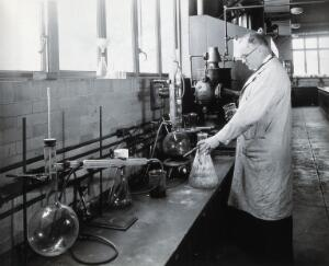 view Philadelphia College of Pharmacy and Science: man in a lab. Photograph, c. 1933.