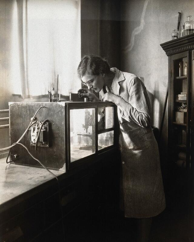 Philadelphia College of Pharmacy and Science: a woman inspecting a microscope in a tank. Photograph, c. 1933.