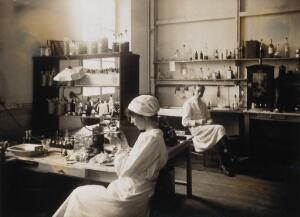 view Military Hospital V.R. 76, Ris-Orangis, France: nurse examining a small object with a magnifying glass. Photograph, 1916.