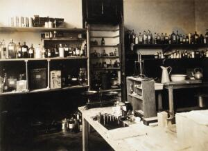 view Military Hospital V.R. 76, Ris-Orangis, France: room with bottles, measuring scales and weights, possibly the pharmacy. Photograph, 1916.