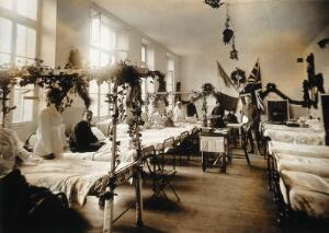 view Military Hospital V.R. 76, Ris-Orangis, France: hospital ward, decorated, with French and British flags. Photograph, 1916.