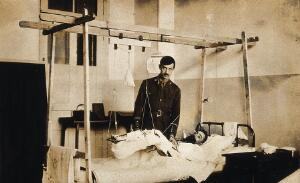 view Military Hospital V.R. 76, Ris-Orangis, France: man with leg in traction, wounded at Verdun in World War I. Photograph, 1916.