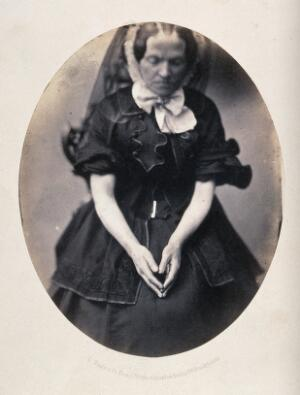 view A woman, seated, wearing a black dress and veil; her hands are in her lap as though she is praying. Photograph by L. Haase after H.W. Berend, c. 1865.