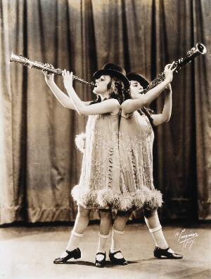 view Daisy and Violet Hilton, conjoined twins, performing with clarinets, wearing top hats. Photograph, c. 1927.