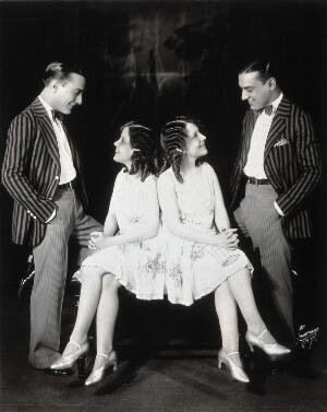 view Daisy and Violet Hilton, conjoined twins, being wooed by two young men. Photograph, c. 1927.