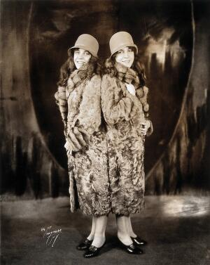 view Daisy and Violet Hilton, conjoined twins, wearing fur coats. Photograph, c. 1927.