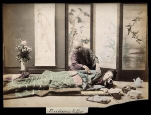 view A Japanese woman being massaged by a blind Japanese masseur. Coloured photograph.