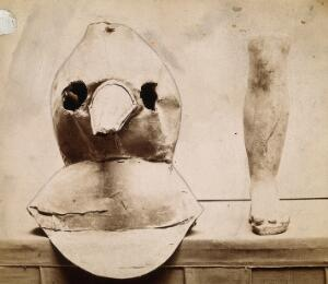 view Plague apparatus from a lazaretto in Venice: an oil cloth mask with a bronze beak and a terracotta model of a foot and leg. Photograph.