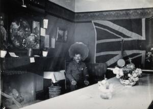 view A soldier sitting in a room in a military hospital in Harrow; there is a huge Union Jack flag on the wall in the background. Photograph, c. 1922.