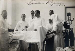 view Swedish surgeon Einar Key (fourth from left) in an operating theatre with other medical staff. Photograph.