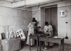 view Artificial limb factory in Rome: two women at wooden workbenches, one with a hammer and one with a drill. Photograph, 1914/1918.