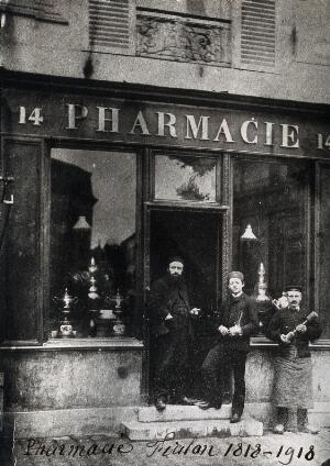 view Two men and a boy wearing hats, standing on the steps of the Pharmacie Fialon in France. Photograph.