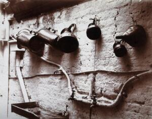 view Measuring jugs and a funnel hung on a wall in the Red Cross pharmacy in London. Photograph.