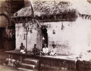 view Four men sitting cross-legged outside a building with bells hanging from the roof: Bombay at the time of the plague. Photograph, 1896/1897.