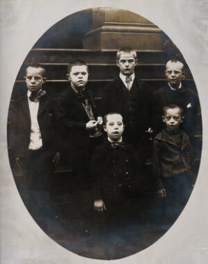 view New York State Institute: a group of boys with Down's syndrome, standing on some steps. Photograph.