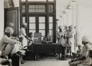 view The Pasteur Institute Hospital, Kasauli, India: Indian patients receiving their daily financial allowance for food; an illiterate patient (right) has his thumb inked to provide a thumb-print receipt. Photograph, ca. 1910.