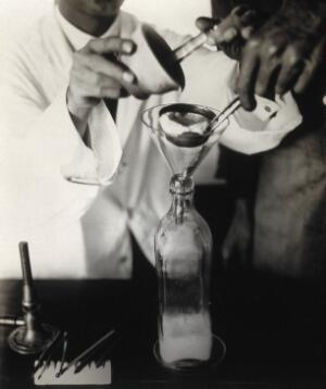 view The Pasteur Institute, Kasauli, India: stages in the preparation of the rabies vaccine: straining an emulsion, made using infected rabbit brain, into a bottle. Photograph, ca. 1910.