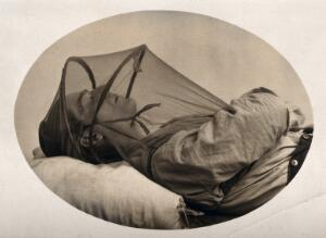 view Mosquito headnet with armholes, covering upper body, modelled by a sleeping man. Photograph, 1902/1918 (?).