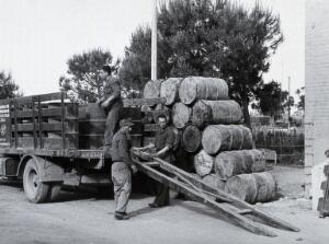 view Malaria control supplies, Italy: large metal barrels being unloaded from a truck by three men. Photograph, 1940/1950 (?).