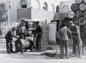 view Malaria control equipment, Italy: men setting up some equipment, with metal barrels of supplies in the background. Photograph, 1940/1950 (?).