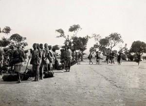 view Tabora, Tanzania: Tanzanian men carrying or standing next to bags. Photograph, 1914/1918.