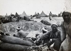 view Sinai Desert, Egypt: Egyptian men in a labour camp; camel and tents in the background. Photograph, 1914/1918 (?).
