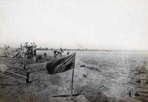 view The junction of the Euphrates river and the Shatt al Arab river, Iraq: (British ?) soldiers on the river bank. Photograph, 1914/1918.
