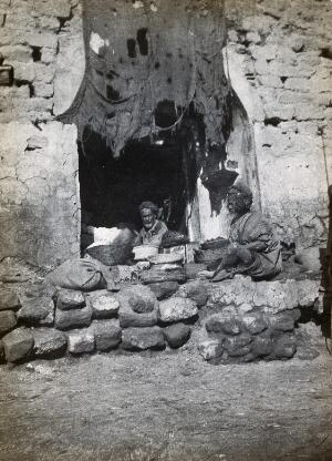 view Shuster (?), Iran: doorway of a shop with two older men in turbans seated next to baskets of produce. Photograph, 1910/1920 (?).