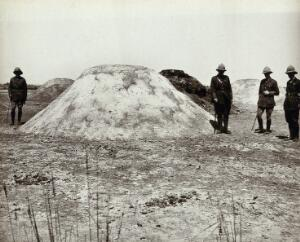 view Mounds of horse-manure coated with sand and oil to prevent fly breeding, with Western (British?) men in military dress, Suez Canal Zone, Egypt (?). Photograph, ca. 1914.