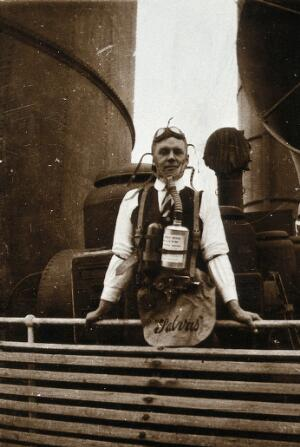 view Ship fumigation using hydrogen cyanide: an operator wearing protective oxygen breathing apparatus. Photograph by P. G. Stock, 1900/1920.