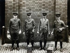 view Liverpool Port Sanitary Authority rat-catchers dressed in protective clothing with traps and equipment, Liverpool, England. Photograph, 1900/1920.