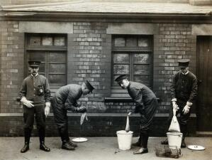 view Liverpool Port Sanitary Authority rat-catchers dipping rats in buckets of petrol to kill fleas for plague control. Liverpool, England. Photograph, 1900/1920.