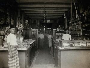 view Kuala Lumpur, Malaysia: a food shop with Malay staff, showing open sacks and boxes of produce, in an urban area prone to outbreaks of typhus. Photograph, 1915/1925.