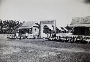 view The James M. Patton Leper Village, Chiengmai Leper Asylum, Thailand: Thai royalty and politicians stand at the entrance with asylum doctors; patients are seated. Photograph, 1921.
