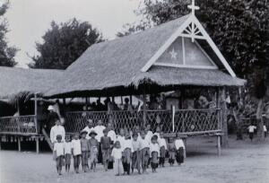 view Chiengmai Leper Asylum, Thailand: children outside the grass-roofed temporary school for uninfected children of leper patients. Photograph, 1921.