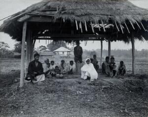 view Assam, India: a kala-azar out-patient centre: a small group of men, women and children sit beneath a grass-roofed shelter with some metal bowls (for heating water for sterilisation ?). Photograph, 1900/1920 (?).