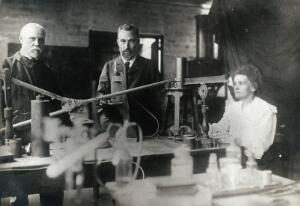 view Marie and Pierre Curie (centre) with a man, using equipment in their laboratory, Paris. Photograph, ca. 1900.