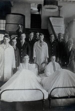 view First World War wounded soldiers (naval?): group portrait: two lying in hospital beds; the remaining standing. Photograph, 1914/1918.