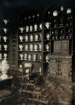 view The old pharmacy of the hôpital Saint-Denis, France: ornate shelving with decorative china pharmacy jars and glass bottles. Photograph, 1890/1910.