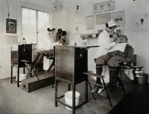 view Dental clinic, U.S.A.: dental hygienists examine two boys seated in wooden dentist chairs; the room is decorated with dental hygiene awareness posters. Photograph, ca. 1920.