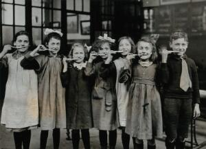 view Tooth-brush drill at school, England: children pose with tooth-brushes in mouth in a school building. Photograph, ca. 1920.