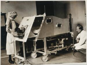 view An iron lung, St. Bartholomew's Hospital, London: a patient inside a Drinker respirator, attended to by a nurse and a doctor. Photograph, ca. 1930( ?).