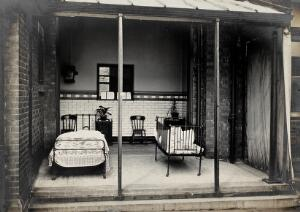 view Nottingham: a verandah open to the air with a bed and a cot, each containing a child being treated for acute illness. Photograph, 1893.