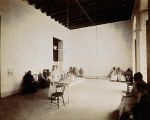 view Waiting room in a dispensary for the treatment of tuberculosis, Cuba: a nurse stands beside the reception table, surrounded by seated patients. Photograph, 1902.