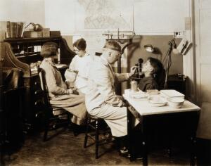 view A Pennsylvania State tuberculosis clinic: a male doctor is shown examining the tongue of a young boy, while a female medical practitioner takes the pulse of a woman. Photograph, 1925/1935?
