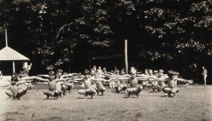 view Children doing outdoor exercises at the Mont Alto Sanatorium for tuberculosis, Pennsylvania: the children are stripped to the waist and some show the effects of heliotherapy on their skin. Photograph, 1920/1940?