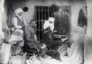 view Sudan: barbering, tooth-drawing and cupping being practised. Photograph, ca. 1920.