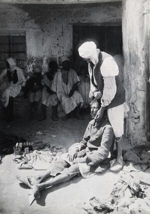 view Sudan: an operator holding a tooth extracted from a man seated in the street. Photograph, ca. 1920.