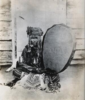 view Siberia: a Tungus medicine man in ceremonial dress, seated holding a drum. Photograph, ca. 1920 (?) of a photograph by Marya Czaplicka, 1914/1915.